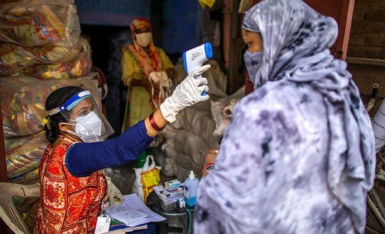 Vandana Gupta, a community worker with SEWA, checking body temperature as part of COVID-19 safety protocols at a ration distribution centre in Jahangir Puri, New Delhi, India.