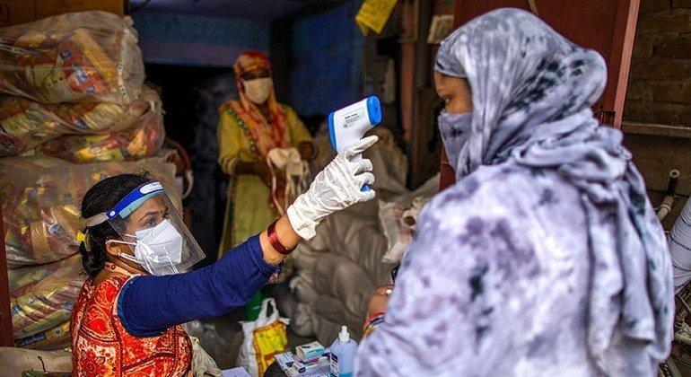 Vandana Gupta, trabajadora comunitaria de SEWA, comprueba la temperatura corporal como parte de los protocolos de seguridad de COVID-19 en un centro de distribución de raciones en Jahangir Puri, Nueva Delhi, India.
