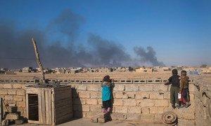 أطفال في العراق ينظرون من خلال الحائط لسحب دخان ناجمة عن احتراق آبار النفط بفعل داعش.