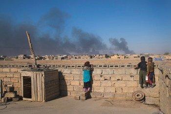 من الأرشيف: أطفال في العراق ينظرون من خلال الحائط لسحب دخان ناجمة عن احتراق آبار النفط بفعل داعش.