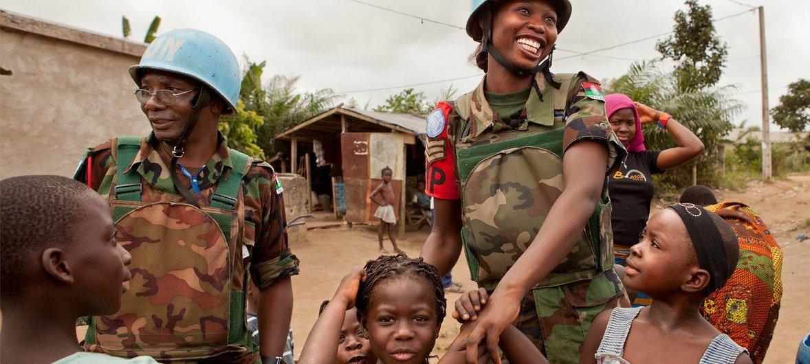आइवरी कोस्ट में संयुक्त राष्ट्र शांतिरक्षा अभियानों में कार्यरत महिला शांतिरक्षक एक गश्त के दौरान बच्चों से मिलते हुए.