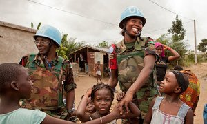 Malawian peacekeepers serving with the United Nations Operation in Côte d'Ivoire (UNOCI) greet children while on patrol in August 2012.