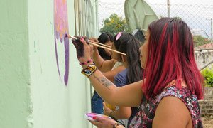 Women in Colombia decorate a wall with messages of peace in the town of  Monterredondo.