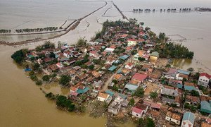 An aerial photograph showing houses destroyed and submerged in flood waters caused by the typhoon in Le Thuy district, Quang Binh province, central Viet Nam.