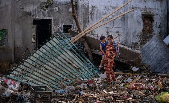 A woman carries her child as she walks past the ruins of a house destroyed by recent floods central Viet Nam. (October 2020)