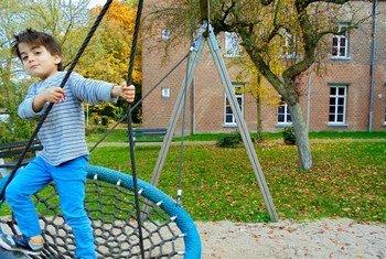 一个男孩在荷兰巴埃克斯姆的一个庇护寻求者中心的操场上玩耍。
