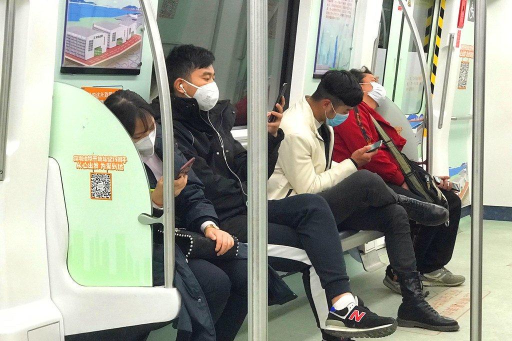 中国深圳的乘客在乘坐地铁时戴着口罩。