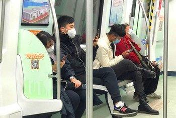 Abiria wakiwa wamejikinga na maambukizi ya mfumo wa hewa wakiwa katika treni za chini ya ardhi huko Shenzhen China