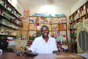 IOM helped Mohammed Ahmed to set up a shop in Omduram market, near Khartoum, Sudan. The initiative involves the use of mobile money to buy goods