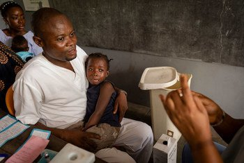 Un enfant est réconforté par un agent de santé alors qu'il attend d'être vacciné contre la rougeole dans un dispensaire du district de Nsele, en République démocratique du Congo (RDC).