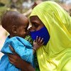 A baby plays with her mother's mask at a nutrition support programme in Bertoua, Cameroon.
