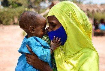 Un bebé juega con la máscara de su mamá en en un centro de apoyo nutricional en Bertoua, Camerún.