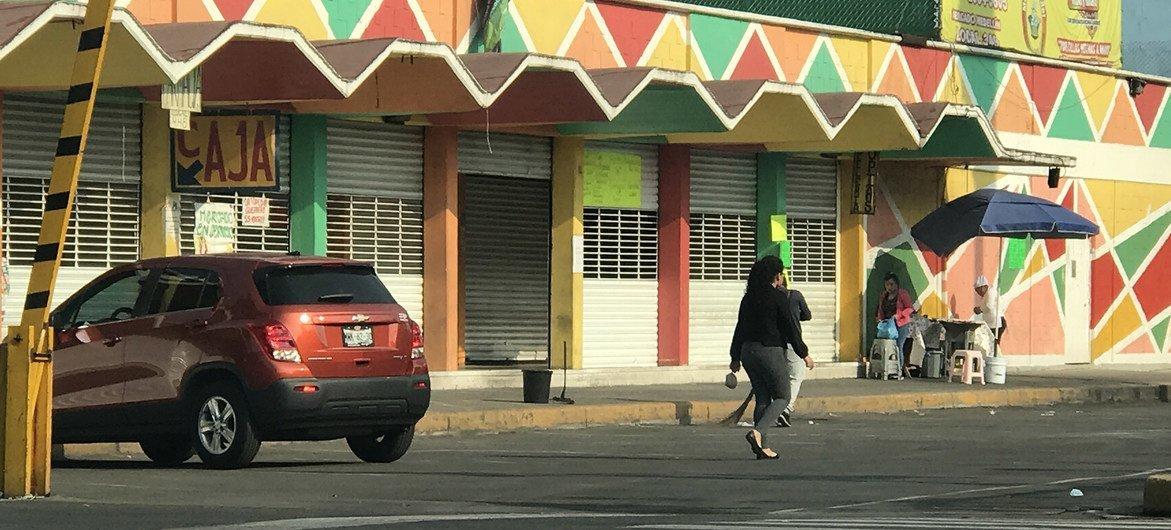 Escenas de la vida cotidiana en la Ciudad de México durante la pandemia de COVID19. En la imagen, una mujer camina por un mercado cerrado.