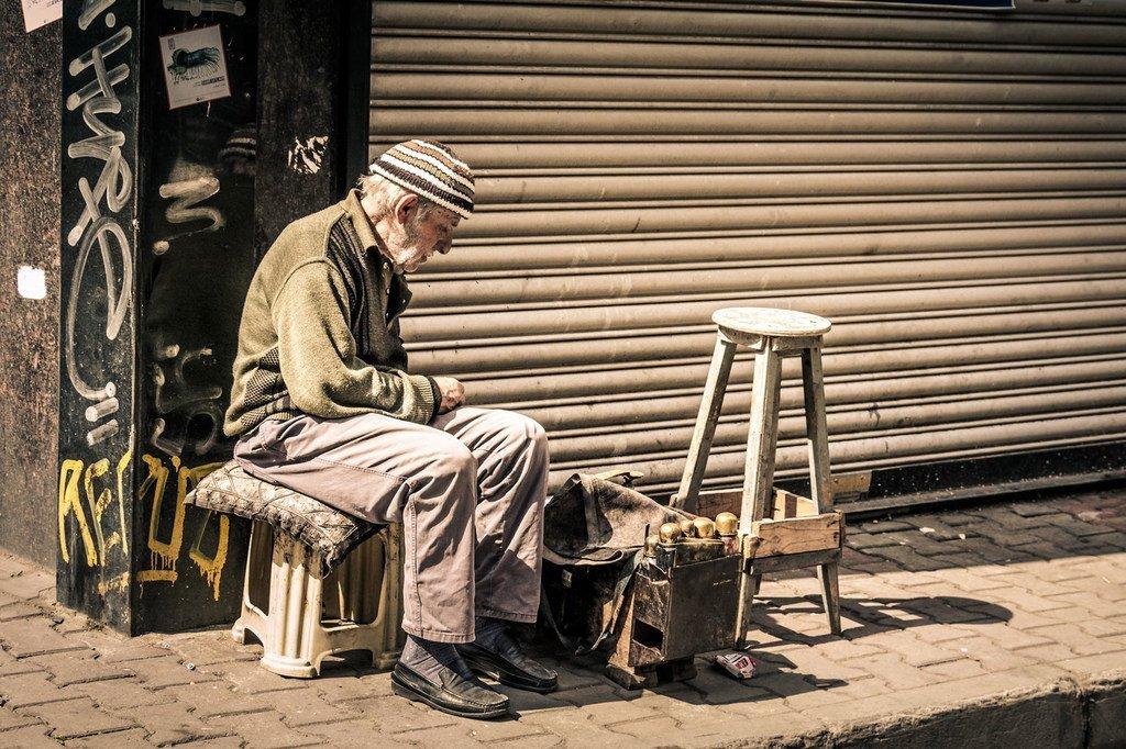Un hombre de edad limpia zapatos en Turquía para mantenerse.