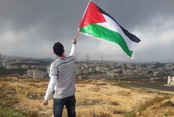 Une jeune homme agitant le drapeau palestinien