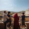 عائلة سورية تقف على شرفة منزلها في سهل البقاع بلبنان قبل أيام من إعادة توطينها في فرنسا.