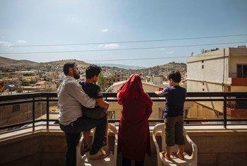 Uma família síria fica na varanda de sua casa no vale de Bekaa, no Líbano, dias antes de ser reassentada na França.