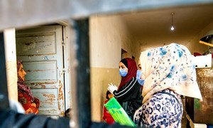 UNICEF-supported volunteers speak with a family about preventive measures to stem the spread of COVID-19 in Hassakeh, Syria.