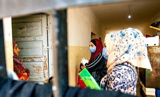 متطوعات تدعمهن اليونيسف يتحدثن مع عائلة حول التدابير الوقائية لوقف انتشار كوفيد-19 في الحسكة، بسوريا.