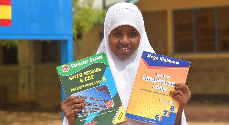 Binti akiwa ameshikilia vitabu msaada wa Umoja wa Ulaya kwa watoto wakimbizi katika kambi ya Dadaab nchini Kenya