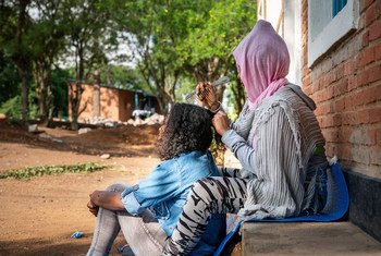 Samrawit, a 20-year-old Eritrean asylum-seeker braids her friend's hair at the UNHCR Emergency Transit Centre in Gashora, Rwanda.