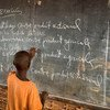 A young Burundian refugee completes an exercise on a blackboard at Jugudi Primary School in Nyarugusu Refugee Camp, Kigoma Province, north-west Tanzania. (February 2019)