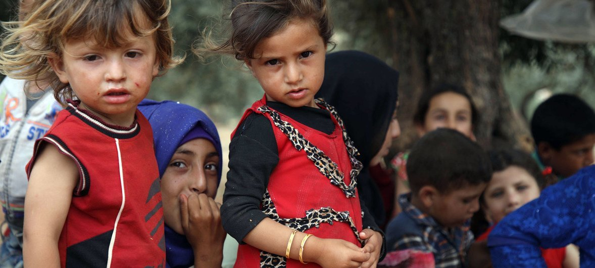 Children rest beneath a tree in a makeshift camp in Aqrabat village, near the Turkish border, after fleeing hostilities in Idlib. (June 2019)