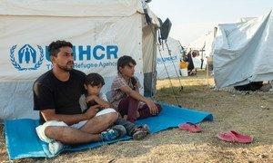 رجل من أفغانستان (33 عاما) يجلس مع أفراد من أسرته في أحد المخيمات على جزيرة ليسبوس اليونانية، ويامل في نقله إلى ألمانيا.