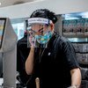 A woman employee, wearing a mask and face shield, works at a shopping centre, in Bangkok, Thailand. According to UN Women, women labour force participation is about 60 per cent in the country.