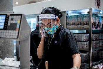 Una mujer trabaja en un centro comercial de Bangkok, Tailandia protegida con una pantalla contra la covid19