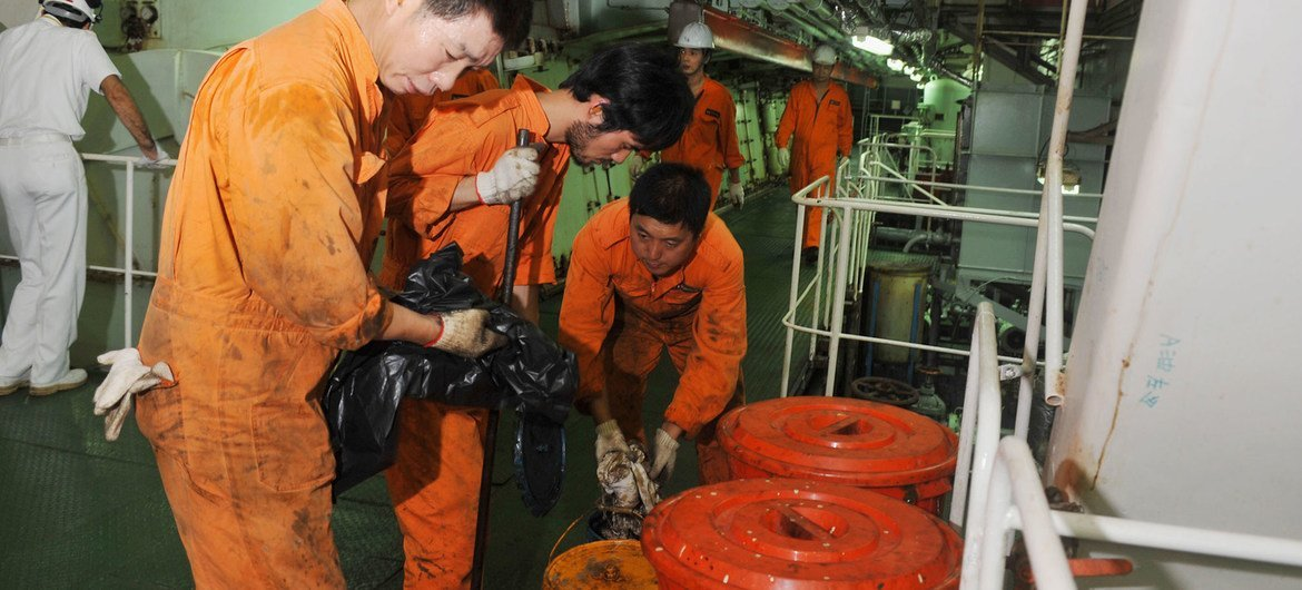 Seafarers work in the engine room of a Chinese registered ship in the Port of Genoa in Italy.