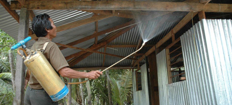 Un ouvrier pulvérise de l'insecticide sur les surfaces d'un abri pour contrôler la propagation des moustiques et atténuer le risque de paludisme