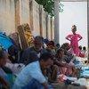 इथियोपिया से विस्थापित शरणार्थी सूडान के पूर्वी इलाक़े में बनाए गए एक शिविर इलाक़े में, धूप से बचने के लिये दीवार की छाया में बैठे हुए.