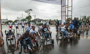Des athlètes libériens handicapés avancent leur fauteuil roulant vers la ligne de départ d'un mini-marathon de 10 km pour les personnes handicapées dans le centre de Monrovia, au Libéria.