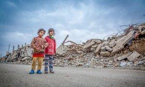 فتاتان تسيران على أنقاض مبان مدمرة في مدينة الموصل في العراق.