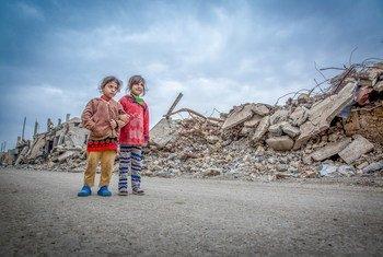 Watoto wawili wa kike wakitembea katika mji ulioharibiwa wa Mosul nchini Iraq