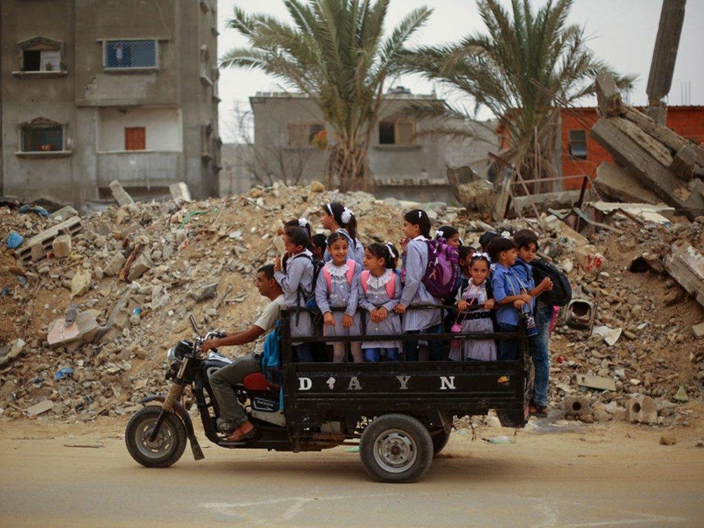 أطفال فلسطينيون يستقلون مركبة (توك توك) في طريقهم إلى المدرسة