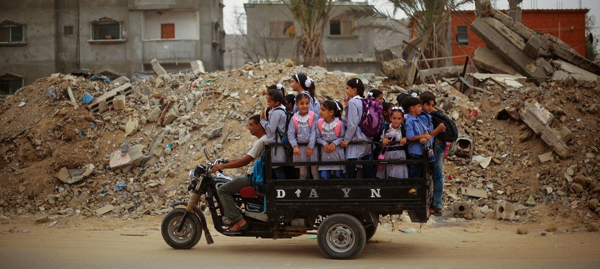 Palestinian children ride a tuk-tuk (modified motorcycle and miniature pickup) on their way to school.