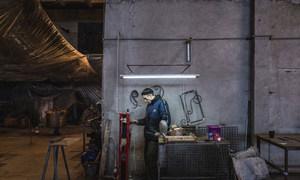 乌克兰东部因冲突而流离失所的一名工人正在金属加工厂修理机器。