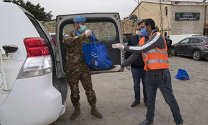 Un Casque bleu de la Force des Nations Unies au Liban (FINUL) remet des équipements pour affronter le Covid-19 à la municipalité de Naqoura, où se trouve le quartier-général de la FINUL.