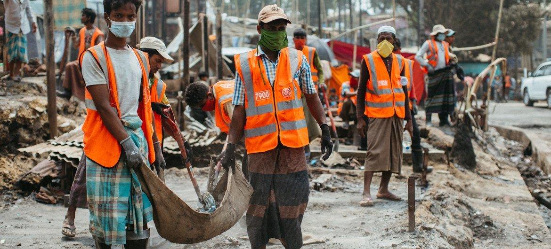 Membro da minoria rohingya se voluntaria para limpar destroços para reconstruir abrigos após um incêndio no campo de refugiados de Kutupalong, em Cox's Bazar, Bangladesh.