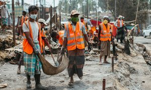 Rohingya volunteers clear debris to reconstruct shelters after the devastating fire at the Kutupalong refugee camp, in Cox's Bazar, Bangladesh.
