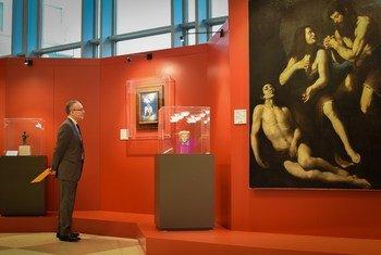 Visitante da exposição junto de um dos quadros recuperados pelas forças italianas