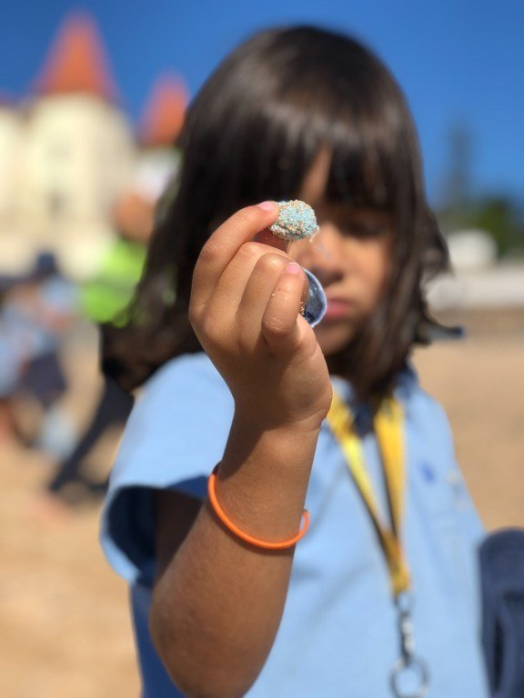 Children cleaning Praia da Poça, a popular little beach at the start of the Estoril - Cascais coast, in Portugal.