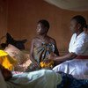 A woman who has had no prenatal care, and whose child was stillborn, is comforted by a nurse in the maternity ward of a hospital in Sierra Leone.