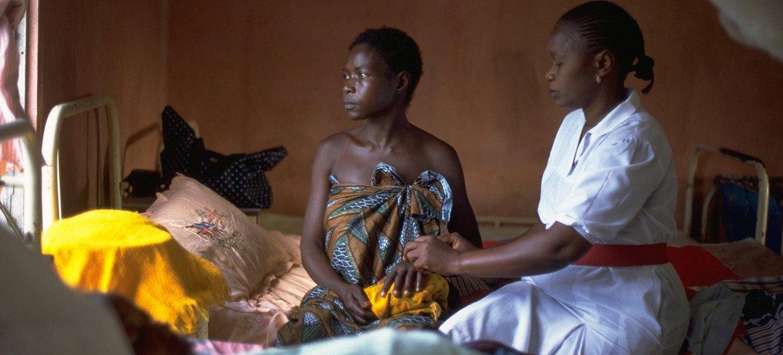 Kadiatu Sama, ambaye hakupata huduma yoyote ile wakati wa ujauzito na ambaye mwanae alizaliwa mfu, akiwa anafarijiwa na muuguzi wa kike kwenye wodi ya wazazi ya hospitali ya serikali nchini Sierra Leone.