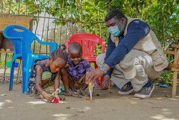 Olea Balayulu, un psychologue soutenu par l'UNICEF, tente d'aider David et Louise Ilomba, âgés de 7 et 6 ans, face à leur chagrin après la mort de leur maman à cause d'Ebola. (Equateur, RDC 2018).