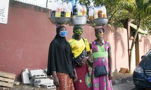 Three young women wearing masks are selling medicine on the street during the COVID-19 crisis in Abidjan, Côte d'Ivoire.