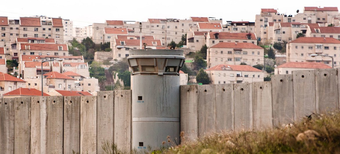 The Separation Wall in the occupied Palestinian Territory and behind it an Israeli settlements.