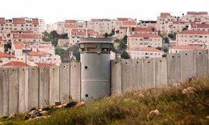 جدار الضم وخلفه مستوطنة إسرائيلية.